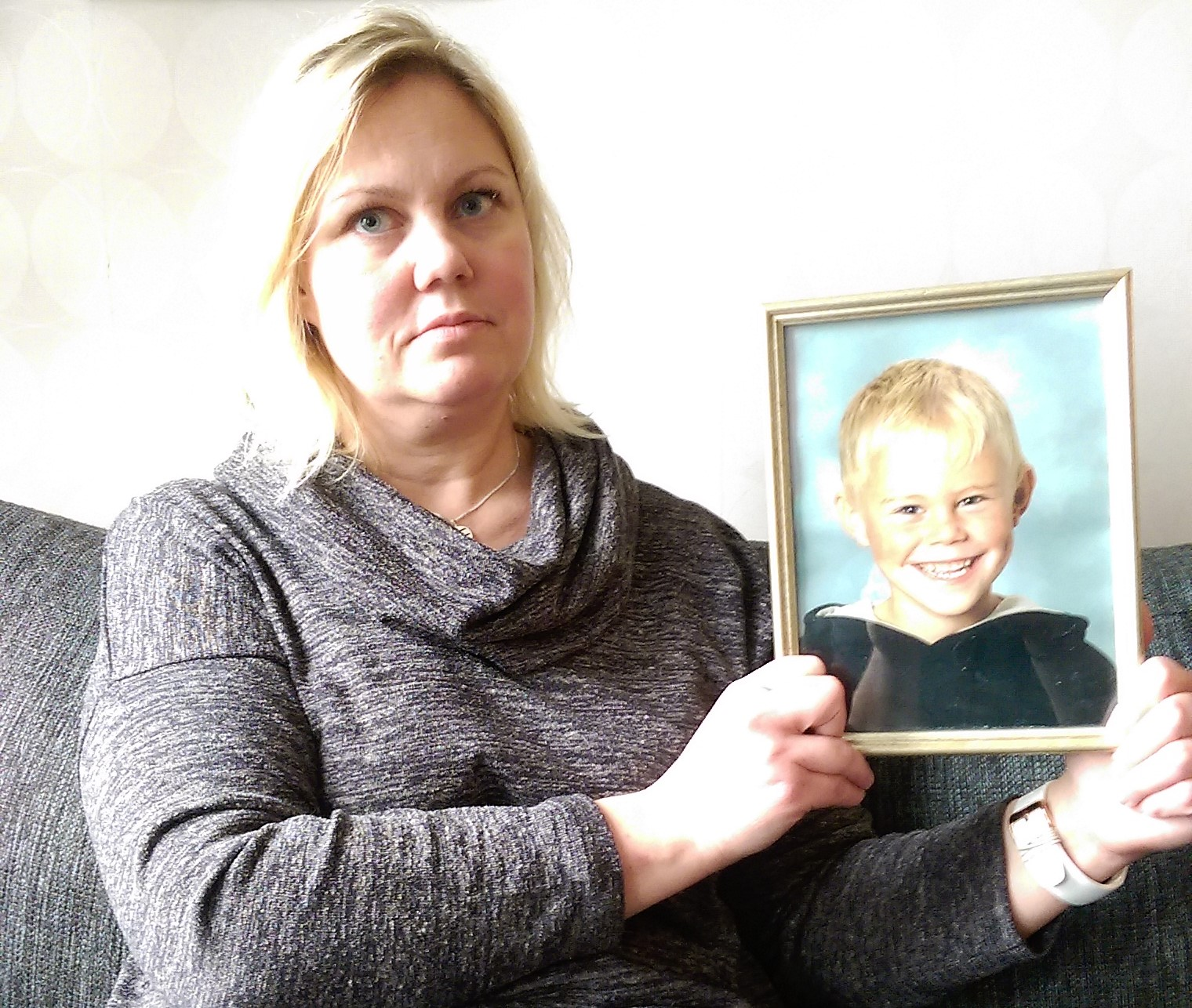 Carola med ett foto på sin son som liten. Foto: privat.